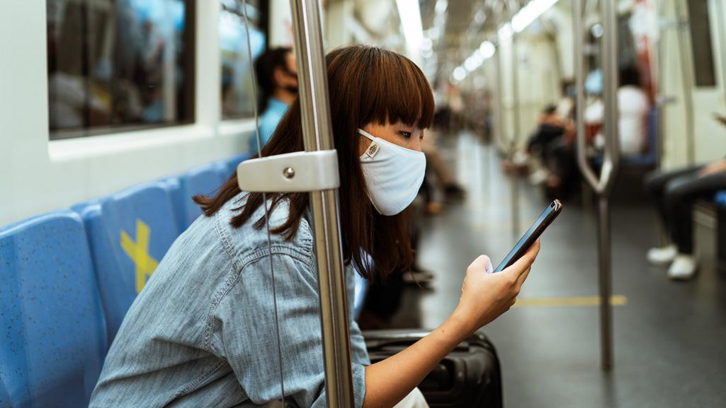 Frau mit Handy in der U-Bahn