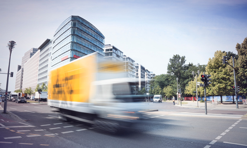 At a junction passes a yellow truck at high speed (motion blurred) with Office buildings in the background and trees on the right.